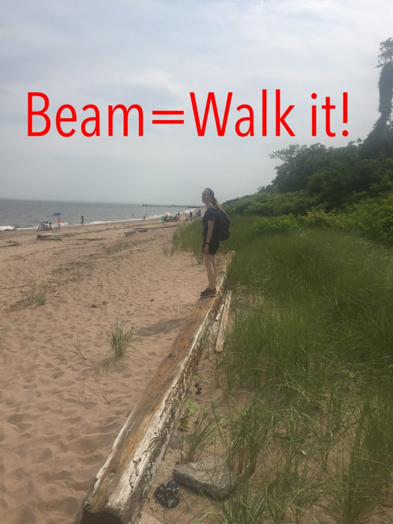 Photo of Heather walking a beam on the beach.